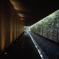 Grand entrance: Kengo Kuma combined bamboo clad-walls, stone paving, a bamboo hedge and the building's deep eaves to create this walkway at the entrance of the Nezu Museum, which opened last year in Tokyo. | © MITSUMASA FUJITSUKA