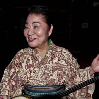 Keeping it real: Misako Oshiro tunes up her sanshin after an impromptu decision to play at her minyo (folk song) club Shima Umui in Naha, Okinawa Prefecture.  | STEPHEN MANSFIELD