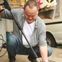Mr. Yoshinaga sprays a toy clean with a pressure washer. | EDAN CORKILL PHOTO