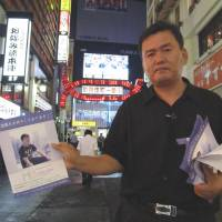 Campaign goes on: Sung-won Kang hands out flyers in Kabuki-cho while visiting  Tokyo in 2011 to find information about the death of his son, Scott Kang, who was found comatose in a stairwell the entertainment district on Aug. 24, 2010. He died six days later. | SIMON SCOTT