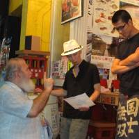 Seeking answers: Kang family friend Ray  Wozniak hands out flyers in Kabuki-cho while visiting  Tokyo in 2011 to find information about the death of Scott Kang. | SIMON SCOTT
