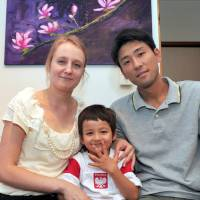 Creative couple: Karina and Masaki Ota pose with their son, Emil, at their apartment in Tokyo. A painting by Karina hangs on the wall behind them. | YOSHIAKI MIURA