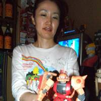 Flashy and fascinating: Ayako Otsuka, owner of a tiny Gundam-themed bar in Shinjuku's Golden Gai (above). Below: Gundam from behind