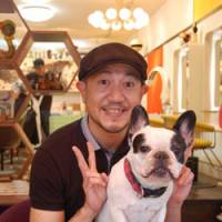 Daylong companion: Toru Sakuma with his bulldog Bu, one of five dogs that keep customers company at the Copan hair salon in Nogata, Tokyo.