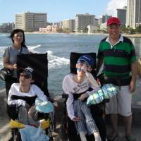 Taking it higher: Motoko and Nobuo Yamaguchi (rear left and right) with their sons Takahiro (left) and Kodai enjoy a break in Waikiki, Honolulu, 2008. Although the Yamaguchis always follow protocol, which includes submitting information on their sons' disabilities in advance, Takahiro and Kodai were almost unable to board a plane to Okinawa because the batteries in their life-supporting equipment were considered a possible security risk. | YAMUGUCHI FAMILY PHOTO