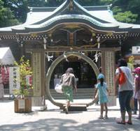 Ring of confidence: Visitors step through a circle of thick cogon- grass rope in a rite supposed to purify them before they walk on to worship at the island's Hetsunomiya Shrine behind.