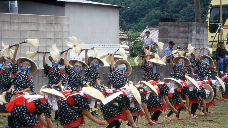 Rice-maidens, donned in bright outfits and bamboo hats, perform the rice-planting dance.
