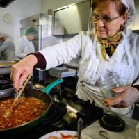 What's cooking?: Volunteers from Catholic charity Caritas prepare meals in the San Benedetto parish kitchen in Rome on May 28. | AFP-JIJI