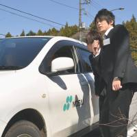 Thumbs up: Two new employees attempt to hitch a ride on April 12 in Fujikawaguchiko, Yamanashi Prefecture, during a training program for new recruits. | KYODO