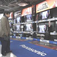Spoiled for choice: A customer looks at Panasonic Corp. Viera televisions displayed at an electronics store in Tokyo in February. | BLOOMBERG