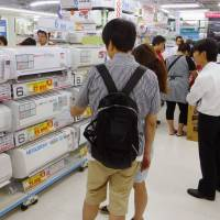 Sales soar: Customers check out air conditioners at Bic Camera's flagship electronics store in Ikebukuro, Tokyo, on Friday. | KYODO