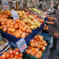 Shipped direct: A shopper looks at fruit outside a Tokyo supermarket. Consumers in other parts of Asia may be able to order fruit like this online if the Trans-Pacific Partnership stimulates global trade. | BLOOMBERG