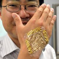 Skintight: University of Tokyo professor Takao Someya displays the world's lightest and thinnest flexible integrated circuits and touch sensor system for stress-free wearable health care sensors Wednesday in Tokyo. | AFP-JIJI