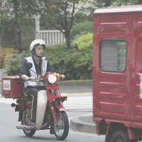 Follow the leader: A Japan Post Co. employee follows a delivery van on a motorcycle near a branch office in Tokyo on June 19. | BLOOMBERG