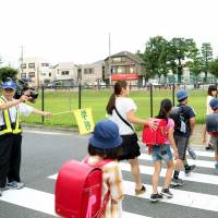 Watchful: Parents accompany students to Oizumi Daiichi Elementary School in Nerima Ward, Tokyo, on Monday, the first school day following a knife attack on three boys last week. A 47-year-old man was arrested over the assault. | KYODO