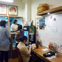 Working together: At Sign with Me, a cafe owned and operated by staff with hearing disabilities in Bunkyo Ward, Tokyo, messages are written on a white board. | KYODO