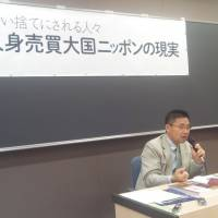 Outing abuses: Ippei Torii, secretary-general of the Solidarity Network with Migrants Japan, speaks at a symposium Saturday in Tokyo on human trafficking. | TOMOHIRO OSAKI