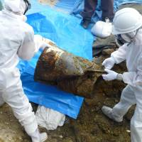 Uneasy unearthing:  Workers dig out decayed barrels that may have contained toxic agents used during the  Vietnam  War from a soccer ground that was once part of the U.S. military's Kadena Air Base in the city of Okinawa on  Tuesday. | KYODO