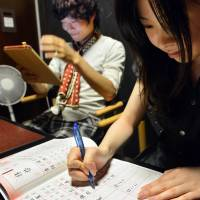 The new and the old: University student Akihiro Matsumura uses his tablet computer while a friend practices kanji in a copybook in Tokyo on June 19. | AFP-JIJI