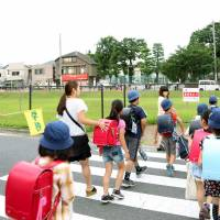 Safety in numbers: Students go to school in groups Monday in Nerima Ward, Tokyo, after three boys were attacked there June 28. At far left is Isamu Hiroto, 71, the crossing guard who fought with the assailant. | KYODO