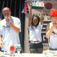 With relish: Takeru Kobayashi (right) competes in a hot dog eating contest he organized Thursday in New York. | KYODO