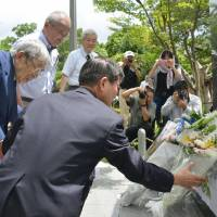 Atonement: Former Nagasaki Mayor Hitoshi Motojima (left) places flowers Sunday at a new monument in the city of Nagasaki commemorating Chinese who died from the atomic bombing in August 1945. | KYODO