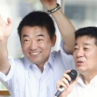 Glad-handing: Nippon Ishin no Kai co-leader Toru Hashimoto (left) and Secretary-General Ichiro Matsui wave to voters in Osaka at the start of Upper House election campaigning Thursday. | KYODO