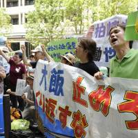 Heating up: People protest electric utilities' applications for restarting nuclear reactors at the Nuclear Regulation Authority's headquarters Monday morning in the Roppongi district of Tokyo. | KYODO
