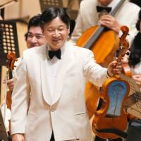 No ordinary driftwood: Crown Prince Naruhito displays a viola Sunday at a concert held by Gakushuin University alumni in Tokyo. The viola was partially built from a pine tree hit by the March 2011 tsunami in Rikuzentakata, Iwate Prefecture. | POOL
