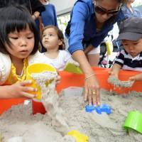 Inside job: Kids play with the indoor Dancing Sand kit during a June promotional event in Tokyo's Shibuya Ward. | KYODO