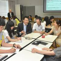 Corporate input: Tatsuo Hirase (third from left) of Mitsui & Co. holds a group discussion at Aichi Prefectural University, where he delivered a lecture in June. | CHUNICHI SHIMBUN