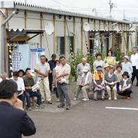 One issue: Evacuees living in temporary housing in the city of Fukushima listen to a stump speech July 4 as the Upper House election officially kicked off. | KYODO