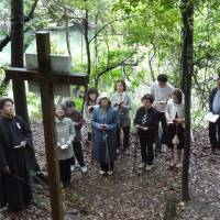 Stations of the cross: Participants in a program combining meditation with Bach's music pause before a crucifix outside a Catholic church in Munakata, Fukuoka Prefecture, on June 2. | KYODO