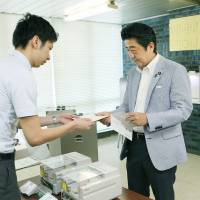 Early bird: Prime Minister Shinzo Abe hands an absentee ballot for Sunday's Upper House election to an official in Shibuya Ward, Tokyo, on Tuesday. | POOL