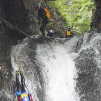 Not so gently: Adventurers slide down a waterfall in Minakami, Gunma Prefecture, on June 10. | KYODO