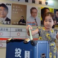 The youth vote: A girl casts a vote in front of posters for major political parties at the Kidzania career theme park in Tokyo on Friday. Children took part in a mock vote to learn about the political process ahead of Sunday's Upper House election. | AFP-JIJI