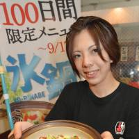 Cool innovations: An employee at the Akakara pub in the city of Nagoya displays the seasonal 'ice pot dish' it serves in the summer. | CHUNICHI SHIMBUN