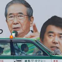 Familiar faces: A taxi passes by a poster in Tokyo for Nippon Ishin no Kai (Japan Restoration Party) showing co-leaders Shintaro Ishihara and Osaka Mayor Toru Hashimoto. | AP