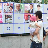 Family affair: A couple stand with their daughter in front of a board showing the candidates running in the Tokyo district for Sunday's Upper House election, near a polling station in Minato Ward. | YOSHIAKI MIURA