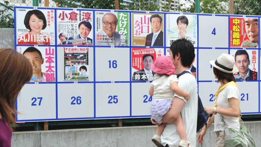 Family affair: A couple stand with their daughter in front of a board showing the candidates running in the Tokyo district for Sunday's Upper House election, near a polling station in Minato Ward.