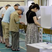 Just the ticket: Voters fill out their ballots for the House of Councilors election on Sunday in Minato Ward, Tokyo. | KYODO