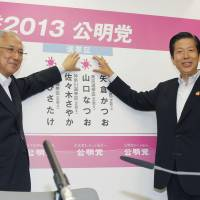 Vote of confidence: New Komeito leader Natsuo Yamaguchi (second from right), who held his Upper House seat Sunday, places a sticker above his name with other senior party members at party headquarters in Shinjuku Ward, Tokyo. | KYODO