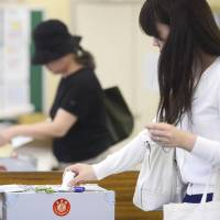 Choosing a winner: Two women vote Sunday at a polling station in Minato Ward, Tokyo. | KYODO