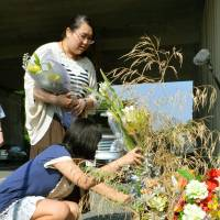 Roadside memorial: Ayano Hayashi (standing) mourns her mother Tuesday at the site of the April 2012 bus crash on the Kan-Etsu Expressway in Fujioka, Gunma Prefecture, that took her life. | KYODO