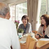 Hometown helpers: Mamoru Kondo and Mariko Tada talk with an elderly resident at a temporary housing site in tsunami-hit Otsuchi, Iwate Prefecture, on June 7. The two are among a growing number of young people who are returning to their hometowns in the Tohoku region to support recovery from the natural disasters of March 2011. | KYODO