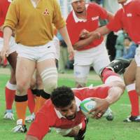 Latu, a Sanyo Electric Co. team member, scores a try during the 1995 national championship held in Tokyo. | KYODO