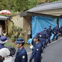 Mass murder: Police on Wednesday enter the Shunan, Yamaguchi Prefecture, home of a 63-year-old man being sought in connection with the Sunday-Monday slayings of five people in the hamlet and two home arson fires believed linked to the murders. | KYODO