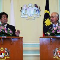 On the same page: Prime Minister Shinzo Abe holds a news conference with his Malaysian counterpart, Najib Razak, in Malaysia's administrative capital of Putrajaya on Thursday. | AFP-JIJI