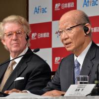 Deal assured: Japan Post President Taizo Nishimuro addresses reporters Friday while Daniel Amos, chairman of U.S. insurance giant American Family Life Assurance Co., looks on as they announce their agreement in Tokyo. | BLOOMBERG