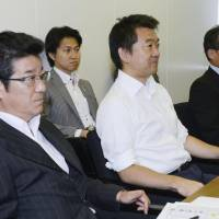 Staying put: Nippon Ishin no Kai co-leader Toru Hashimoto (center) and Ichiro Matsui (left), the party's secretary-general, attend a party meeting Saturday in Tokyo. | KYODO